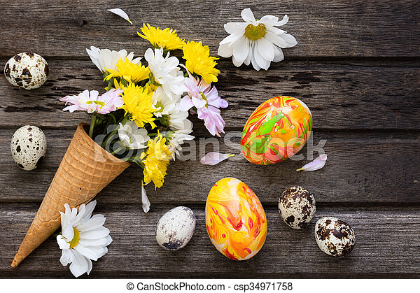 Easter background with eggs and flowers on wooden board, top view - csp34971758