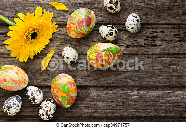Easter background with eggs and yellow flower on wooden board, top view - csp34971757