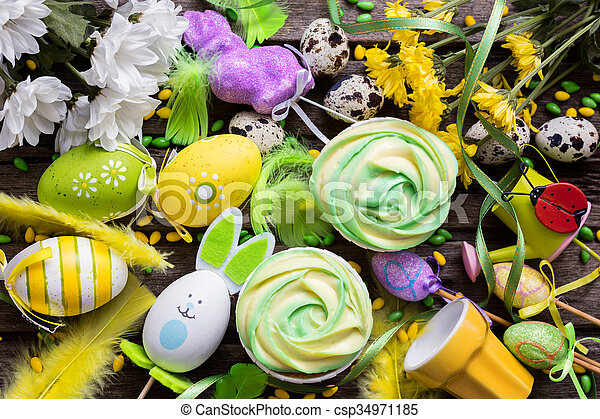 Easter background with eggs, cupcakes, flowers and decoration, top view - csp34971185