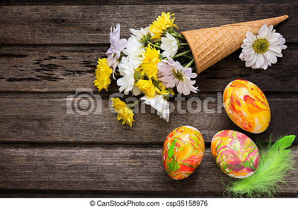 Easter background with eggs, flowers, and decoration on wooden board, top view - csp35158976