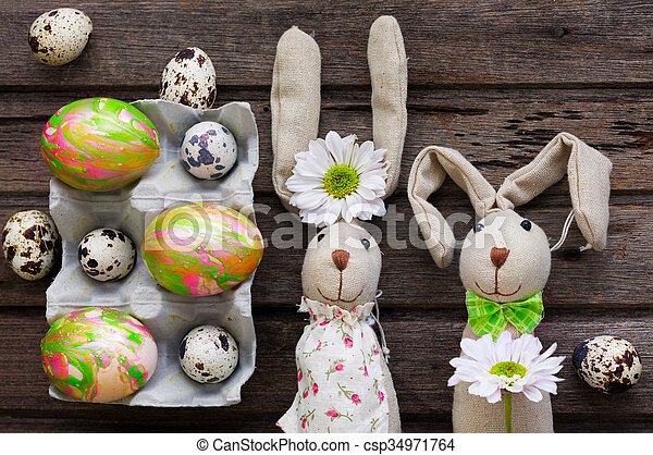 Easter background with eggs, flowers, and home made decoration on wooden board, top view - csp34971764