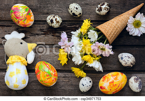 Easter background with eggs, flowers, and home made decoration on wooden board, top view - csp34971753