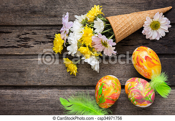 Easter background with eggs, flowers, and decoration on wooden board, top view - csp34971756