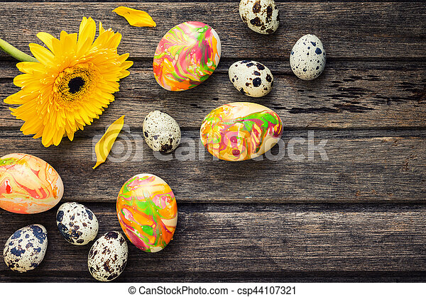 Easter background with eggs, flowers, and decoration on wooden board, top view - csp44107321