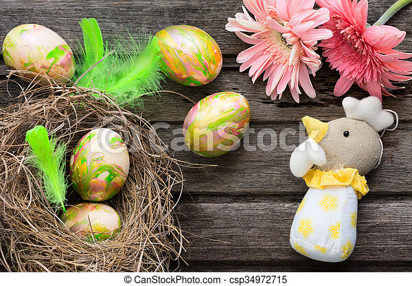 Easter background with eggs in nest and home made decoration on rustic wooden board - csp34972715