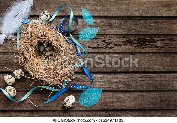 Easter background with eggs in nest on rustic wooden board - csp34971183