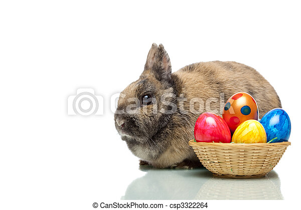 Easter bunny near a basket full of colorful Easter eggs  - csp3322264