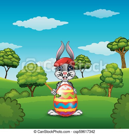 Easter bunny painting Easter eggs in the park - csp59617342