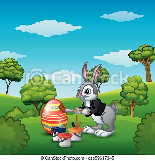 Easter bunny painting Easter eggs in the park - csp59617345
