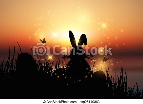 Easter bunny sat in grass against a sunset sky - csp26140863