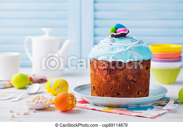 Easter cake with colorful eggs. White and blue wooden background. Copy space - csp69114679