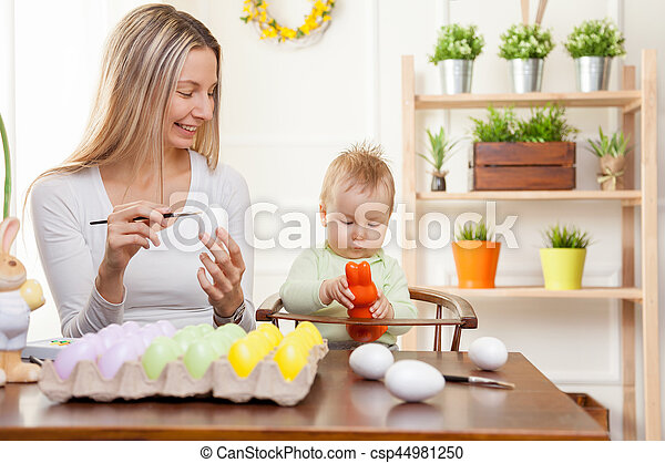 Easter concept. Happy mother and her cute child getting ready for Easter - csp44981250