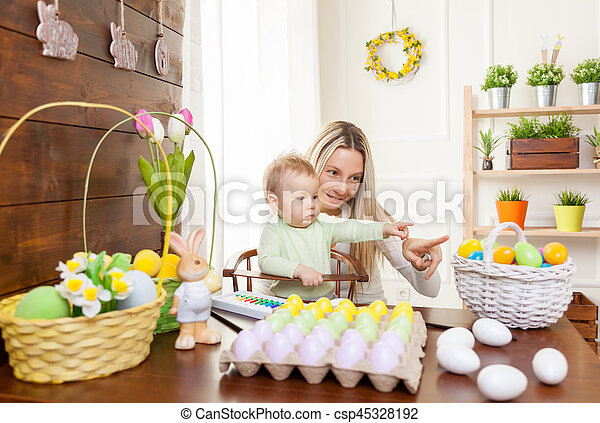 Easter concept. Happy mother and her cute child getting ready for Easter - csp45328192