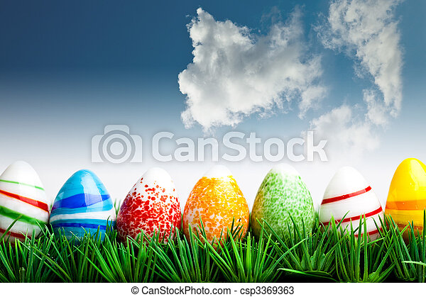 Easter eggs in green grass over blue sky with clouds - csp3369363