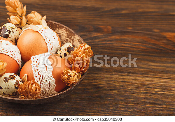 Easter eggs in the bowl, wooden background - csp35040300
