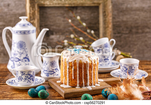 Easter table with Easter cakes and Easter eggs with willow branches. Still life with an ancient frame for a picture in the background. Easter in a rustic style. - csp56270291