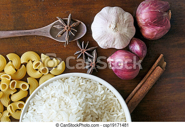 eastern food spice herb rice garlic  red onion cinnamon on wood table background - csp19171481