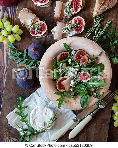 Easy diet salad with arugula, figs and blue cheese on a brown wooden surface. Sandwiches with ricotta, fresh figs, prosciutto, rosemary and blue cheese. Delicious fruity breakfast, top view - csp53130389