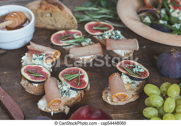 Easy diet salad with arugula, figs and blue cheese on a brown wooden surface. Sandwiches with ricotta, fresh figs, prosciutto, rosemary and blue cheese. Delicious fruity breakfast, top view. Toned. - csp54448060
