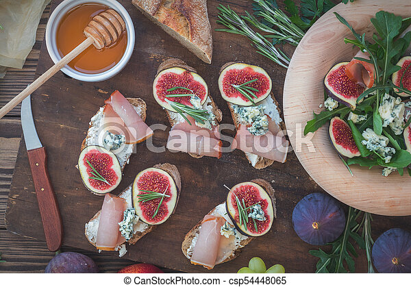 Easy diet salad with arugula, figs and blue cheese on a brown wooden surface. Sandwiches with ricotta, fresh figs, prosciutto, rosemary and blue cheese. Delicious fruity breakfast, top view. Toned. - csp54448065