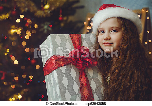 eautiful little girl with gift and in Santa hat. - csp63543058
