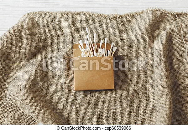 eco natural bamboo ear sticks flat lay on rustic background. sustainable lifestyle concept. zero waste, plastic free items. stop plastic pollution. reuse, reduce, recycle, refuse - csp60539066