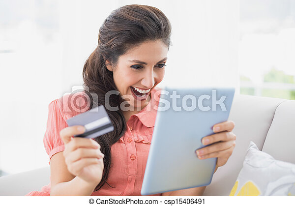 Ecstatic brunette sitting on her sofa using tablet to shop online - csp15406491