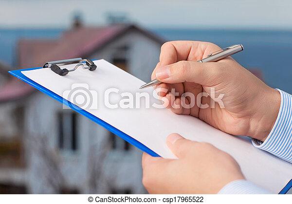 El empresario firma un documento en el fondo de un edificio de apartamentos con cielo azul - csp17965522