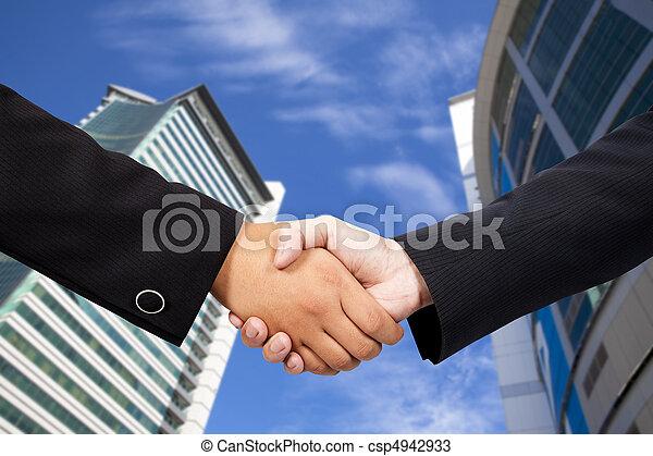 Gente de negocios estrechando la mano contra el cielo azul y el edificio moderno - csp4942933