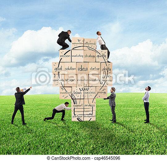 Construyendo una nueva idea creativa. Una persona de negocios construyó un gran muro de ladrillo con bombilla dibujada - csp46545096