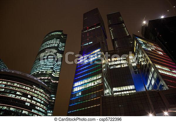 Los pisos de arriba del edificio de oficinas modernos por la noche, rascacielos en Moscú, acelerando desde abajo - csp5722396