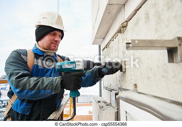 Constructor instalando soporte en la pared de la fachada - csp55554366