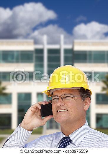 El contratista de Hardhat habla por teléfono frente al edificio - csp8975559