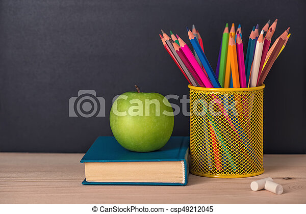 Education Concept With Green Apple Book Pencils Chalks Over Black Chalkboard Background