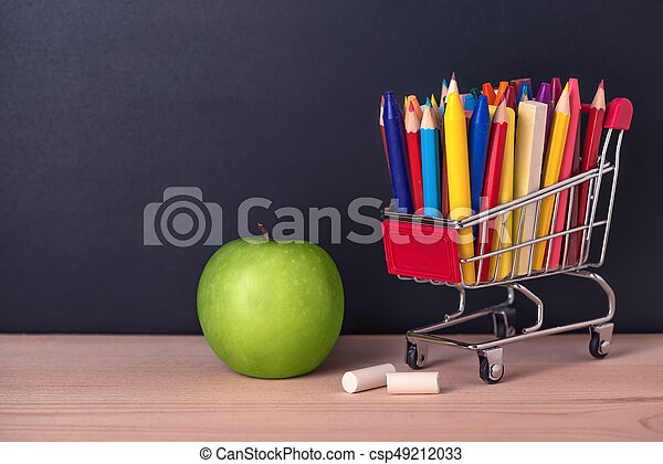 Education Concept With Green Apple Chrome Shopping Cart Pens Crayons Chalks On
