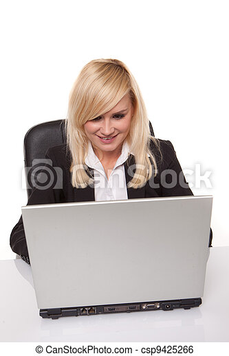 Efficient blonde businesswoman working on her laptop with her spectacles on the table alongside her - csp9425266
