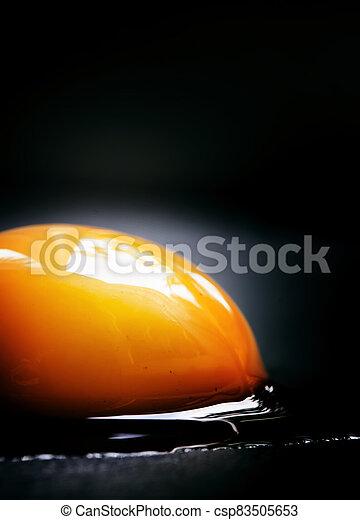 Egg yolk on a dark background, macro shot, selective focus, shallow depth of field - csp83505653