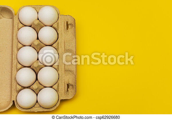 eggs in a cardboard box on a yellow background - csp62926680