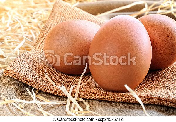 eggs on a burlap bag on a table - csp24575712