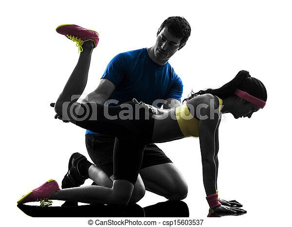 Una mujer ejerciendo ejercicio de posición de tablón con el entrenador - csp15603537