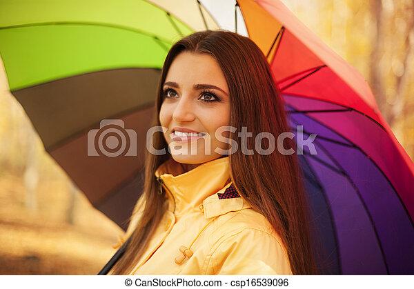 Mujer sonriente bajo el paraguas - csp16539096