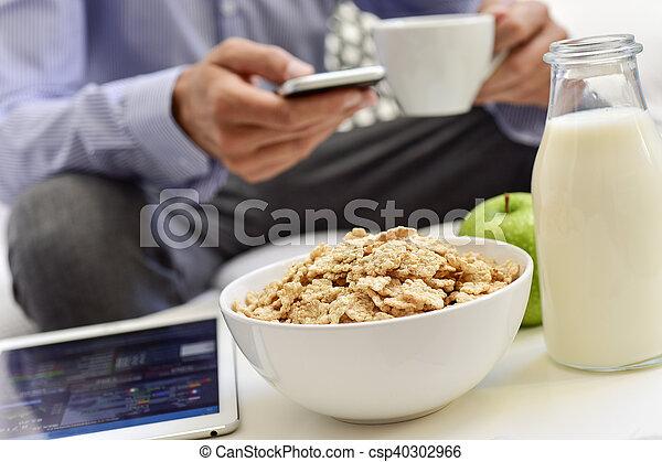 Hombre de negocios revisando su smartphone durante el desayuno - csp40302966