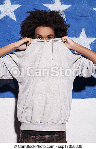 Fresco y joven. Un joven africano escondiendo su cara en su ropa - csp17856838