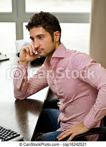 Un joven trabajador guapo o un hombre de negocios en su escritorio - csp16242521