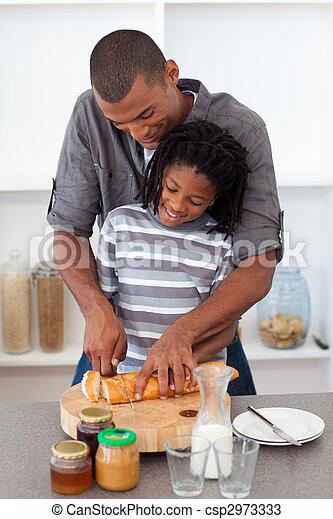 Padre feliz cortando pan con su hijo - csp2973333