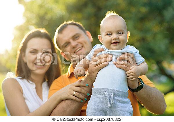 Padres en el parque sosteniendo a su hijo en brazos - csp20878322