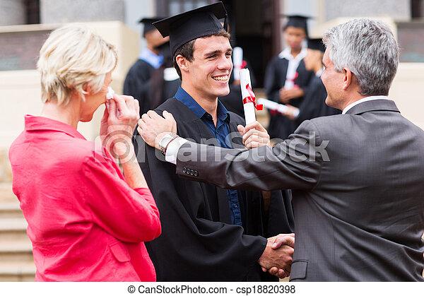 Graduado masculino siendo felicitado por su padre - csp18820398