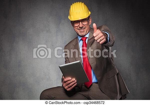 Ingeniero mostrando pulgares arriba mientras sostenía su tableta - csp34468572