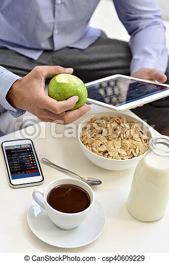 Hombre de negocios revisando su tableta durante el desayuno - csp40609229