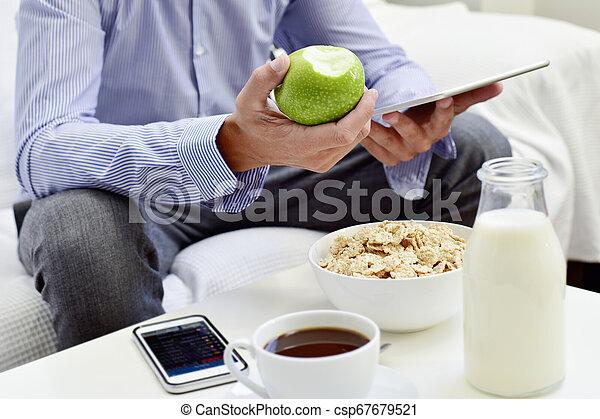 Hombre de negocios revisando su tableta durante el desayuno - csp67679521